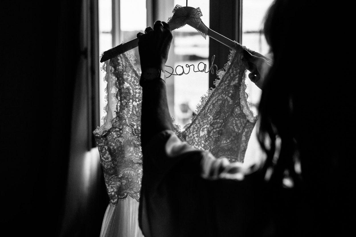 Das Hochzeitskleid der Braut wird von einem Bügel mit dem Namen Sarah getragen
