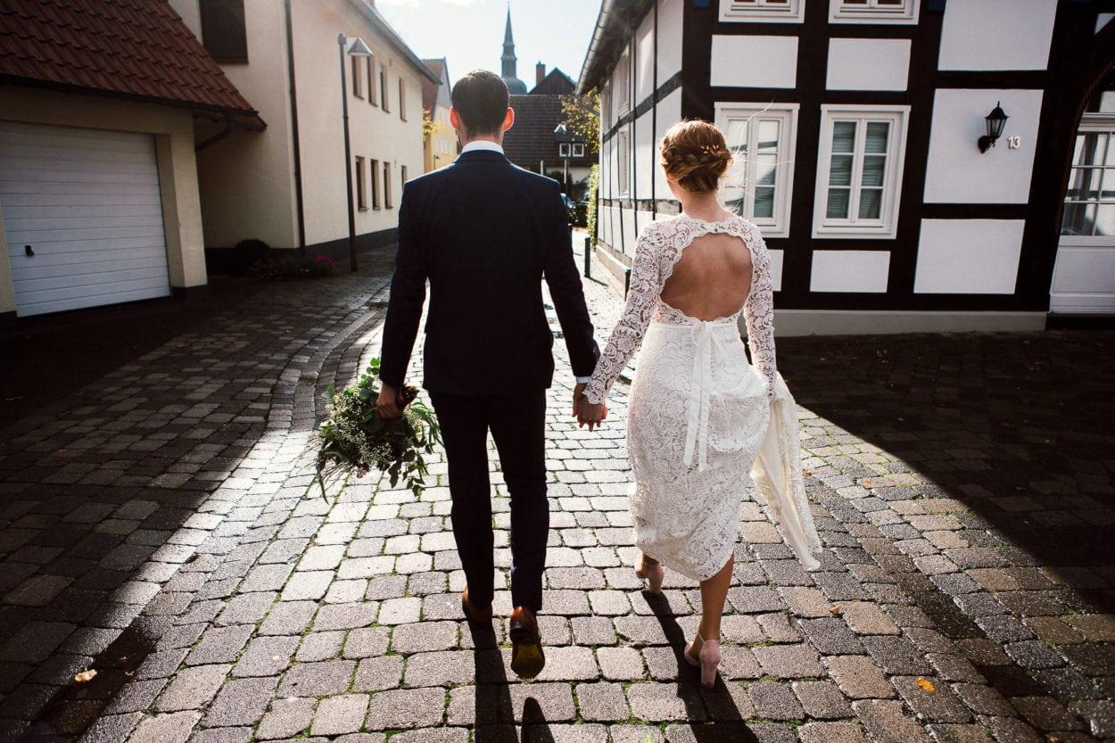 Das Brautpaar spaziert im Sonnenlicht durch Rietberg