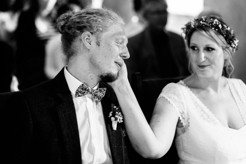 Der Bräutigam legt seinen Kopf auf die Hand der Braut im Schloss Sythen